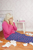 Femme malade s'asseyant contre le lit Photo libre de droits