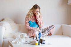 Femme malade s'asseyant dans le sofa images stock