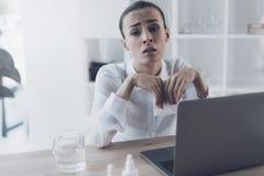 Femme malade s'asseyant sur son lieu de travail dans le bureau Elle repose et tient une serviette de papier dans des ses mains photo stock
