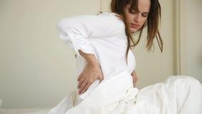 Femme malade se réveillant dans le lit touchant la douleur arrière de sentiment clips vidéos
