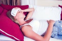 Femme malade se situant dans le lit avec la grosse fièvre Grippe et migraine froides image libre de droits