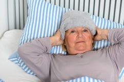 Femme malade se trouvant sur le lit avec la serviette sur le front Photos stock