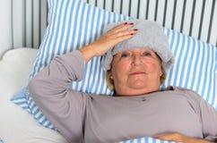 Femme malade se trouvant sur le lit avec la serviette sur le front Image stock