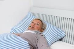 Femme malade se trouvant sur le lit avec le thermomètre dans la bouche Photos stock