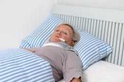 Femme malade se trouvant sur le lit avec le thermomètre dans la bouche Images libres de droits