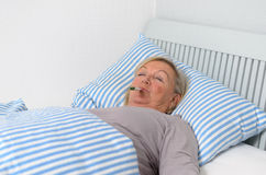 Femme malade se trouvant sur le lit avec le thermomètre dans la bouche Photo libre de droits