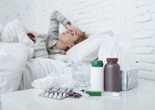 Femme malade sentant le mauvais mensonge malade sur le virus de souffrance de froid et de grippe d'hiver de mal de tête de lit ay Images libres de droits