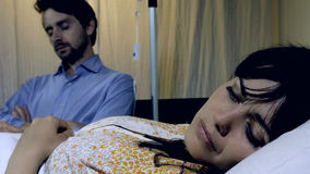 Femme malade triste et songeuse dans l'hôpital avec le mari dormant à côté de elle Images libres de droits