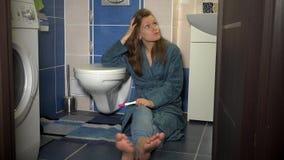 Femme malheureuse avec l'essai de grossesse dans la salle de bains Concept n?gatif positif de r?sultat banque de vidéos