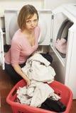 Femme malheureuse faisant la blanchisserie photos stock