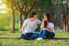 Femme malheureuse s'asseyant avec un type intéressé la soulageant dans le pair Photographie stock libre de droits
