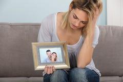 Femme malheureuse tenant le cadre de tableau Images stock