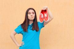 Femme malheureuse tenant une paire de chaussures rouges de sport photos stock