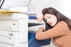 Femme malheureuse triste dans le bureau avec l'imprimante de copieur Photo stock