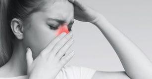 Femme malsaine en douleur touchant sa tête et nez images stock
