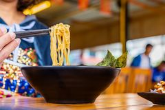 Femme mangeant d'une soupe de nouilles japonaise de ramen épicés dans un bol noir de ramen de couleur images stock