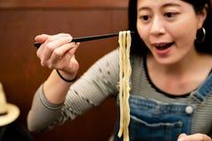 Femme mangeant de l'udon japonais dans une boutique photographie stock
