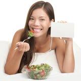 Femme mangeant de la salade affichant le signe de l'espace de copie Photo stock