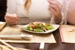 Femme mangeant de la salade dans le restaurant japonais Photographie stock libre de droits