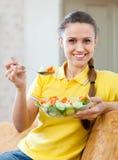 Femme mangeant de la salade de veggie sur le sofa images stock