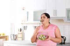 Femme mangeant de la salade végétale dans la cuisine images stock