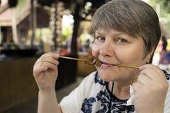 Femme mangeant des moineaux d'un Chinois de chiche-kebab Photos stock