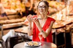 Femme mangeant des moules au marché de nourriture Photographie stock