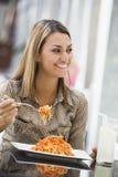 Femme mangeant des pâtes au café Images stock