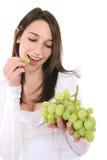 Femme mangeant des raisins Photo stock
