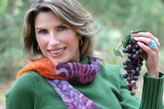Femme mangeant des raisins, thème d'automne Images stock