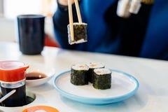 Femme mangeant des sushi avec des baguettes Photo stock
