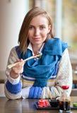 Femme mangeant des sushi dans le restaurant Photo stock
