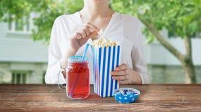 Femme mangeant du maïs éclaté avec la boisson dans le pot de maçon en verre Image stock