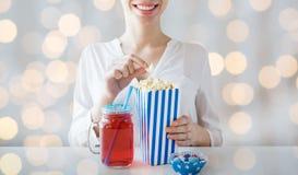 Femme mangeant du maïs éclaté avec la boisson dans le pot de maçon en verre Photographie stock libre de droits