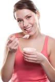 Femme mangeant du yaourt Photographie stock