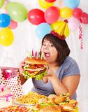 Femme mangeant l'hamburger à l'anniversaire. Photos stock