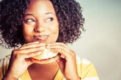 Femme mangeant l'hamburger photo stock
