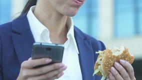 Femme mangeant l'hamburger tandis qu'utilisant le téléphone, mauvaise nutrition due au mode de vie occupé banque de vidéos