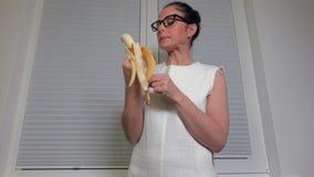 Femme mangeant la banane près de la fenêtre banque de vidéos