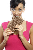 Femme mangeant la barre de chocolat Photographie stock