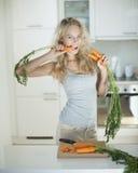 Femme mangeant la carotte au comptoir de cuisine photo libre de droits