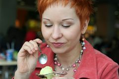 Femme mangeant la crême glacée Photo stock
