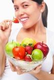 Femme mangeant la fraise et retenant des fruits Photos stock