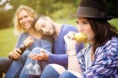 Femme mangeant la poire avec des amis au pique-nique Photographie stock