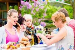 Femme mangeant la saucisse grillée sur la partie de BBQ Photo stock