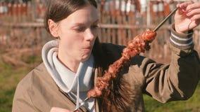 Femme mangeant le barbecue chaud de shashlik de viande sur une brochette dans l'arrière-cour au printemps un jour ensoleillé banque de vidéos