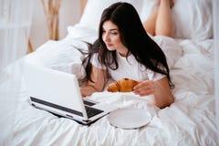 Femme mangeant le croissant et travaillant sur l'ordinateur portable image libre de droits