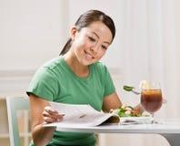 Femme mangeant le déjeuner sain tout en affichant le magazine Image libre de droits