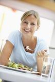 Femme mangeant le déjeuner à un café Image stock