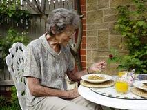 Femme mangeant le petit déjeuner Photographie stock